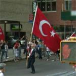 Man walking with a large Turkey flag